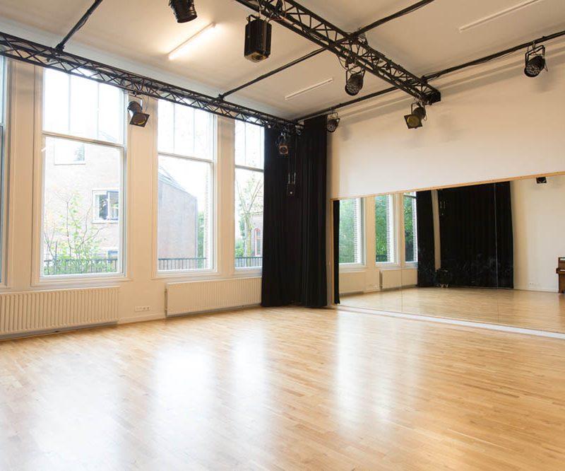 Lege kleine studio met spiegelwand en grote ramen