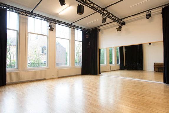 Kleine studio leeg met grote ramen en spiegelwand