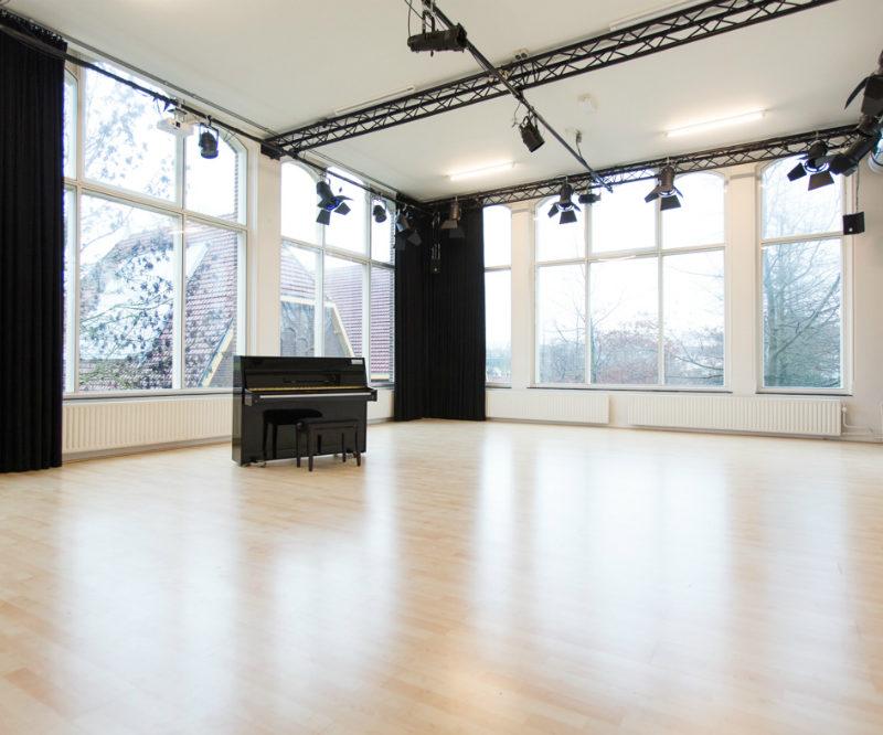 Studio oost leeg met grote ramen en een piano met kruk