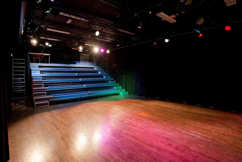 Theaterzaal met uitgeschoven tribune en theaterlampen aan